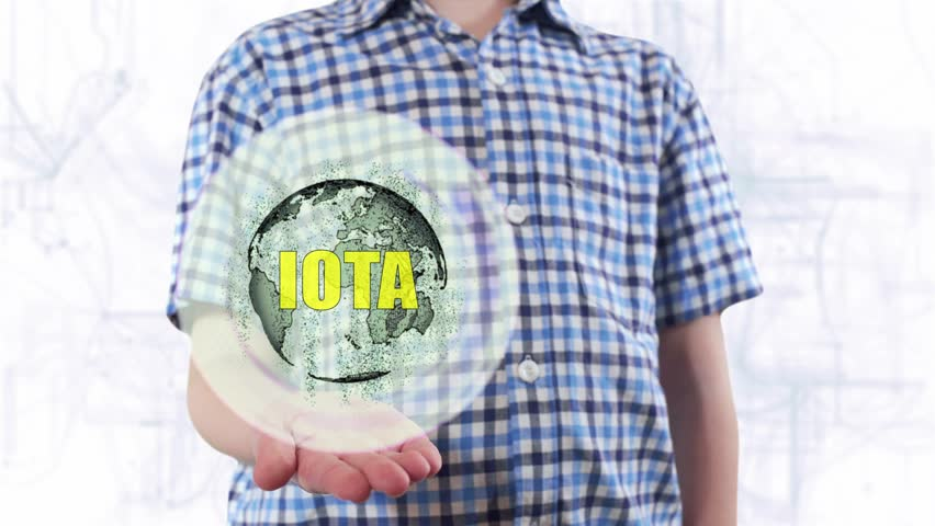 Young man shows a hologram of the planet Earth and text IOTA. Boy with future technology 3d projection on a modern white digital background