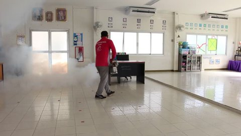 Nakhonratchasima,THAILAND-May 8 2018:A man use fumigation mosquitoes machine for kill mosquito carrier of Zika virus and dengue fever prevention outbreak in school at the rainy season.Soft blur focus.