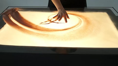 Drawing with sand. Drawing sand on a white screen. Sand Artist. Hands draws