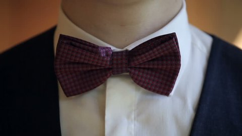 Man straightens bow-tie. Well-dressed young man puts and adjusts classic black bowtie on white shirt. Close up.