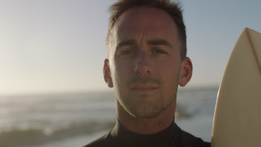 Close up portrait of confident young surfer man smiling cheerful looking at camera, enjoying carefree lifestyle holding surfboard on sunny early morning beach slow motion