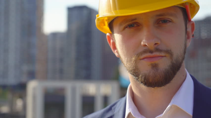 Young attractive man in a yellow hard hat looks into the camera. Portrait of a handsome business man. | Shutterstock HD Video #1010999243