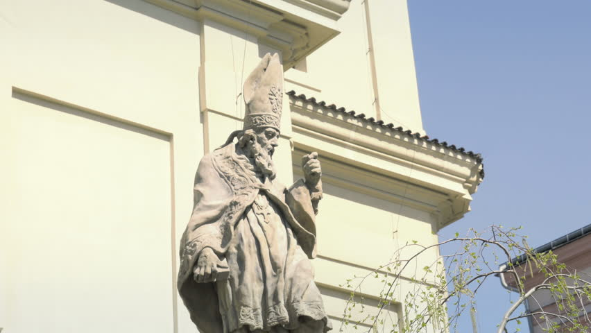 Baroque sandstone statue, Christian holy saint. Beautiful sunny day with blue sky. Stone figure sculpture, church in background. Religious catholic symbolism and scene