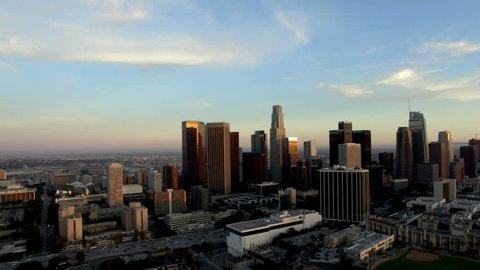 Drone dolly left across downtown LA skyline at dusk