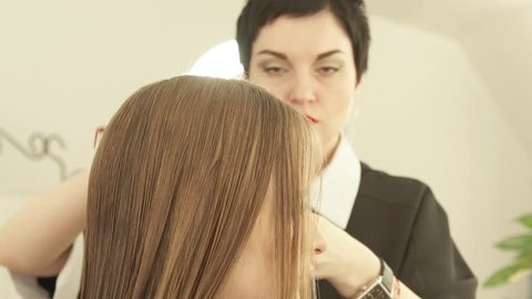 Female hairdresser combing strand hair before cutting young woman in hairdressing salon. Close up haircutter making female haircut in beauty salon