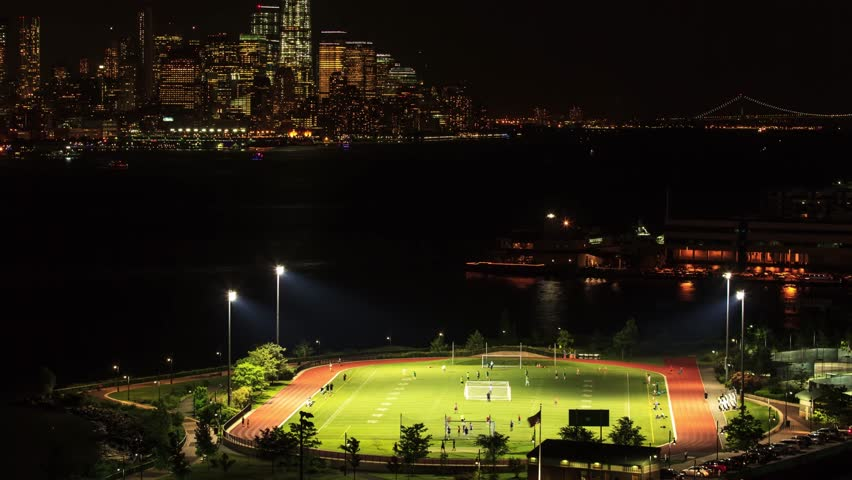 Night timelapse View from WEEHAWKEN New Jersey to Manhattan skyline. people playing soccer on a public field, near the Hudson river.USA | Shutterstock HD Video #1011093593