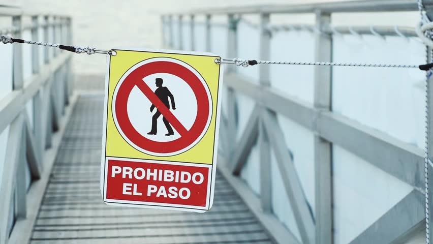No trespassing spanish sign Prohibido El Paso waving in the wind in a sea port.