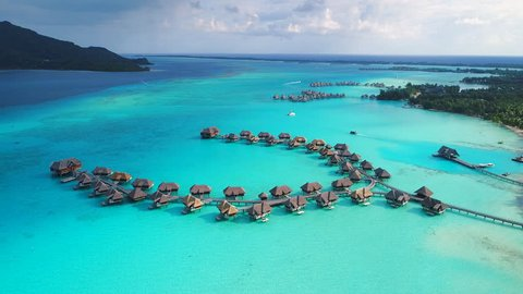 Aerial view of tropical paradise of Bora Bora, turquoise crystal clear water of scenic lagoon, typical overwater bungalows - South Pacific Ocean, French Polynesia, 4k UHD