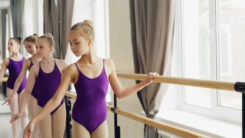 Young ballerinas in trendy ballet suits are practising arm movements and plie in light dancing hall with wooden ballet bar, large mirror and windows.