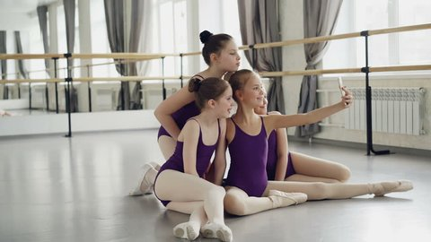 Cheerful children girls in leotards are taking selfie with smartphone and posing looking at camera while sitting on dancehall floor during break in ballet school.