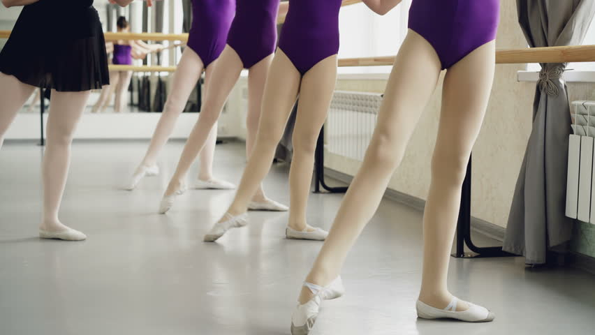 Slim girls' legs in tights are doing battement tendu during ballet lesson with experienced female teacher demonstrating movements and checking her students.
