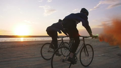 Two young men riding bicycles on the beach with orange smoke during sunset