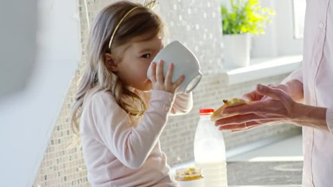 Handheld medium shot of cute little girl sitting on tabletop in kitchen and drinking milk while her cheerful father spreading peanut butter on toast