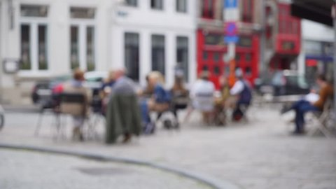 Out of focus background plate of European cafe patio street scene for compositing. Defocused video backdrop of people sitting outside coffee shop for green screen. 4k