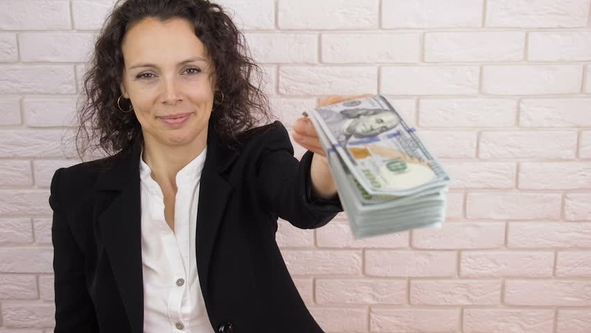 Business woman with money. A woman gives a bundle of money.
