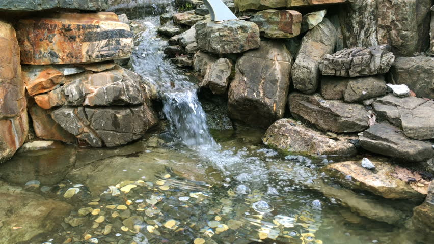 Current clear water stream between stones, or mini-waterfall, which falls into a pond with small coins on the bottom. On a sunny day.