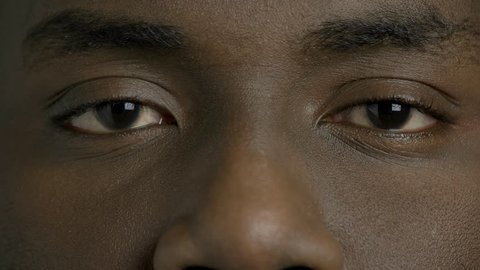 Close up dark-skinned man closed eyes. Afro-american male person is openes his eyes close up. Black man eyes.