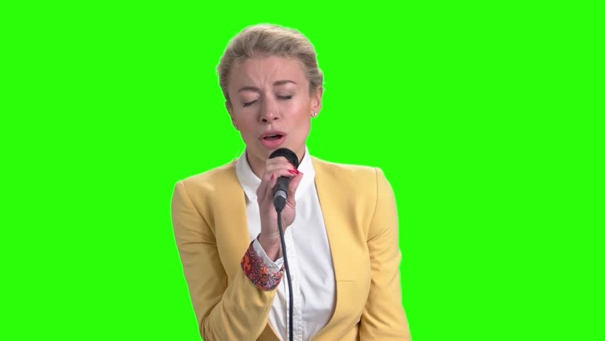 Young pretty blonde singing with microphone. Elegant girl holding microphone and singing on chroma key background. Beautiful caucasian singer.