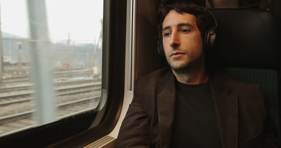 Young man adjusting headphones  while riding train and looking out window on commute, listening to music, audiobook, or podcast