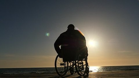 man in wheelchair silhouette near sea horizon at sunset