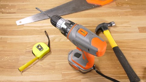 4k workman hands wearing work gloves using a cordless drill with a saw,  tape measure and hammer tools against a wooden workshop background