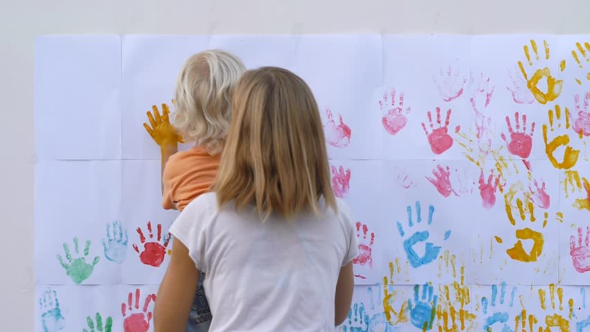 Mother helping her little child to make color handprints on the wall. Funny painting. Slow motion 50fps