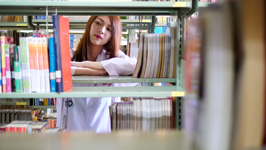 Advertising, Education, Business, Healthcare and Medical Concept - Portrait of smiling beautiful young asian medical student with stethoscope standing near bookshelves in modern interior library. | Shutterstock HD Video #1011280253