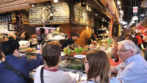 Barcelona, Spain - May 14, 2018: La Boqueria market - Tapas bar serving tourists and locals with traditional Spanish Tapas (Fresh local appetizers