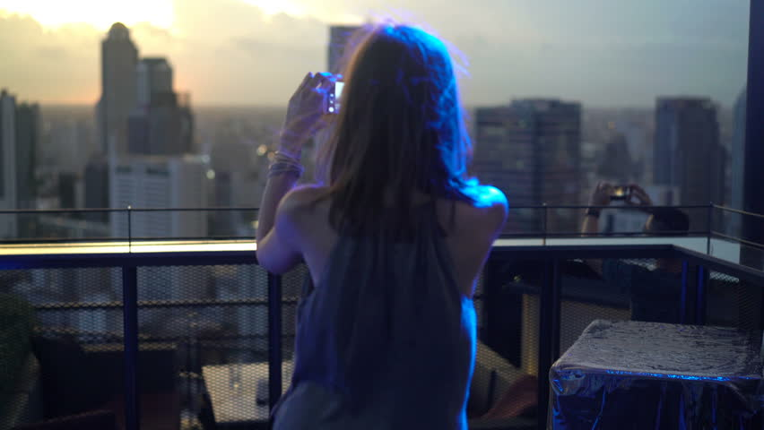 Young woman taking photo of cityscape with cellphone in skybar during sunset  | Shutterstock HD Video #1011288323