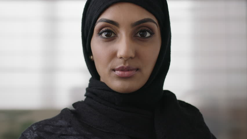 Close up portrait of independent young muslim business woman looking serious confident at camera wearing traditional headscarf slow motion | Shutterstock HD Video #1011299813