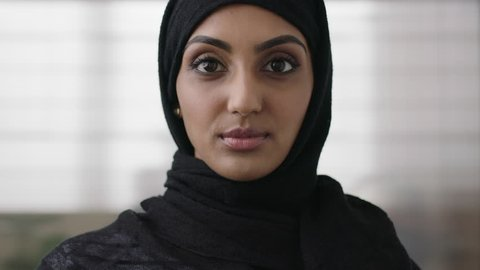 close up portrait of independent young muslim business woman looking serious confident at camera wearing traditional headscarf slow motion