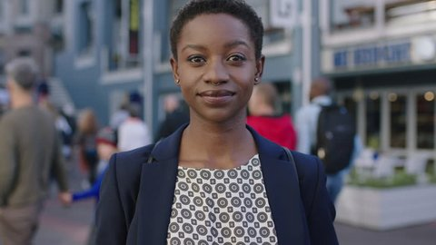 portrait of independent african american business woman looking serious confident at camera in urban background wearing nose ring