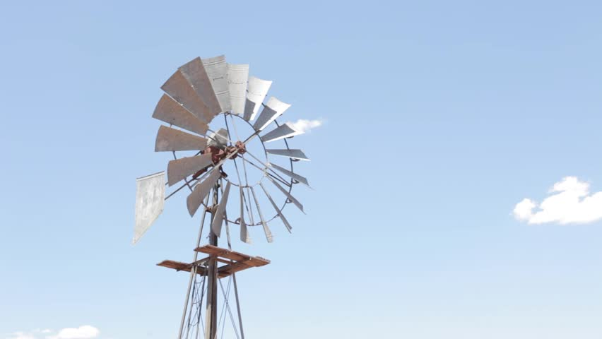 Windmill windpump pumping water stops spinning then turns to catch the wind and starts up again in the dry arid region of the Tankwa Karoo of South Africa.