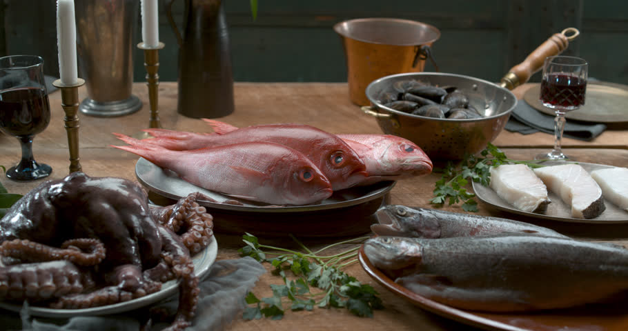 Close up of plates of raw seafood and fish on table to serve. Food cinematic scene.