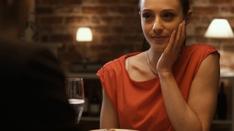 Young happy couple having a dinner date in an elegant restaurant, the woman is smiling and laughing, relationships and lifestyle concept