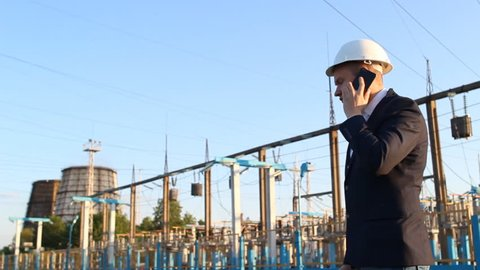 a young engineer looks at the drawing diagram against a power plant background and talks on the phone