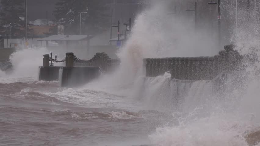 Huge powerful waves breaking at seawall in major severe storm in hurricane force winds   Shutterstock HD Video #1011370553