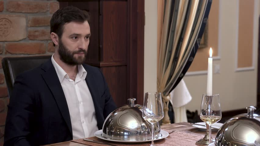 Two waiters simultaneously opens tableware cover - cloche showing the dish in front of the respectable bearded man in a suit. Fine dining restaurant concept.