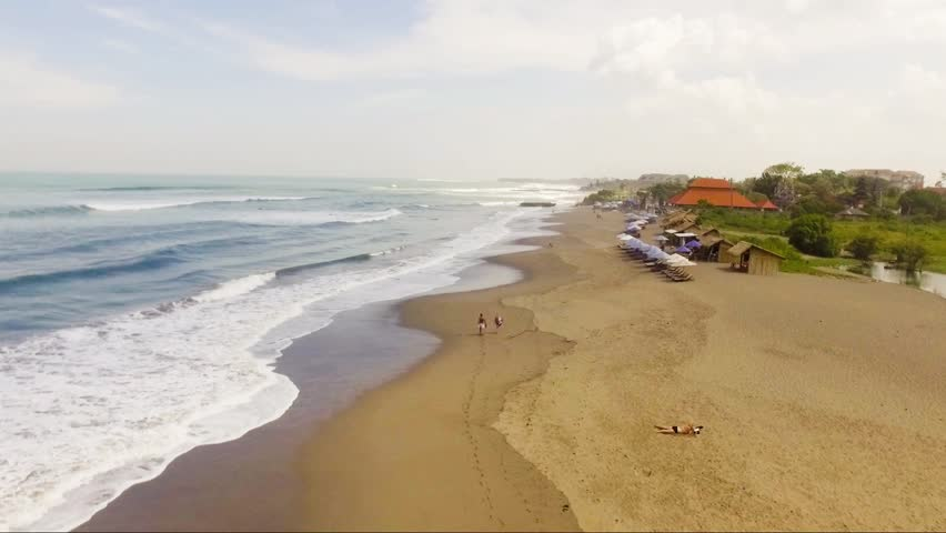 Seminyak Echo beach drone footage Bali with nice waves crashing against the sand closer to the water on a blue sunny day with lots of green trees.