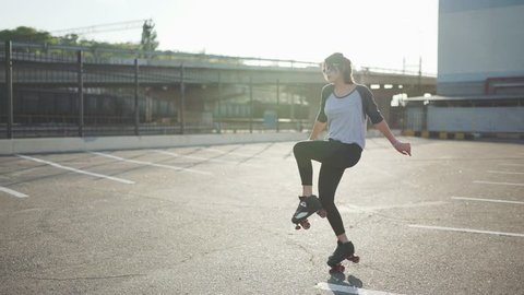 Attractive beautiful young woman riding roller skating and dancing in the streets. Urban background