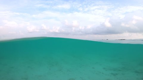 A beautiful tropical beach, half under water - half above water , split shot and in super slow Motion, Maldives Island, Male, Republic of Maldives.
