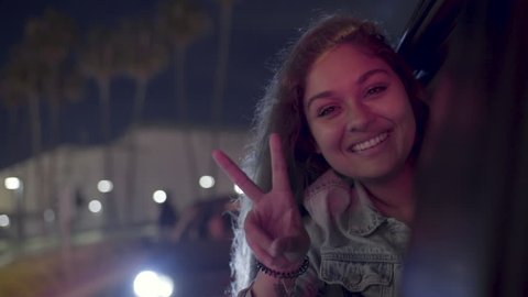 Portrait Of Excited Young Woman Leaning Out Car Window At A Red Light, She Smiles And Holds Up A Peace Sign The Looks Around (Slow Motion)