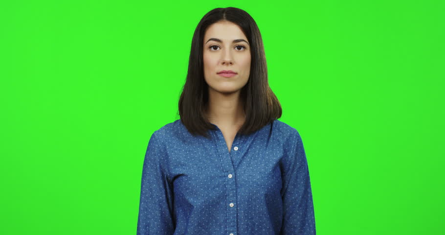 Young brunette attractive woman in the blue shirt standing in front of the camera, saying no and giving her thumb down. Chroma key. Green screen | Shutterstock HD Video #1011449273