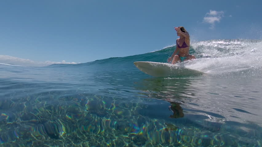 SLOW MOTION, LOW ANGLE, UNDERWATER: Joyful surfer girl carves a glimmering tube wave in spectacular Fiji. Cool young extreme surfboarder rides an amazing big barrel wave during her carefree holiday. | Shutterstock HD Video #1011449363