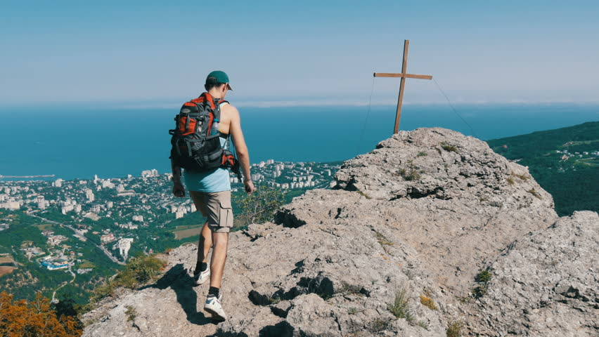 A male traveler with a backpack on his back reaches the top of the mountain, with a cross at the peak. Achievement of the goal, motivation to rise. | Shutterstock HD Video #1011449753