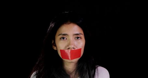 Scared woman with closed mouth using adhesive tape, making silence gesture over dark background. Shot in 4k resolution