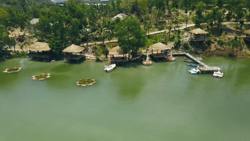 Wooden bungalows with thatched roof and boat pier on shore green lake in resort hotel drone view. Cottages on shore mountain lake among wild nature in water villa resort aerial landscape | Shutterstock HD Video #1011450713