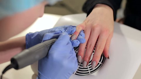 Close-up shot of master uses an electric machine to remove the nail polish during manicure in the salon. Hardware manicure. Concept of body care