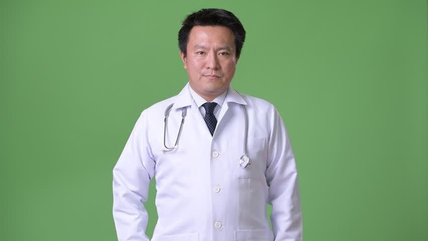 Mature Japanese man doctor against green background | Shutterstock HD Video #1011457133