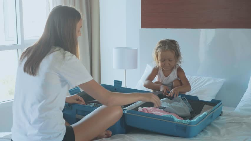 Young with little daughter collecting a suitcase together. The traveling family preparing for journey. | Shutterstock HD Video #1011460103